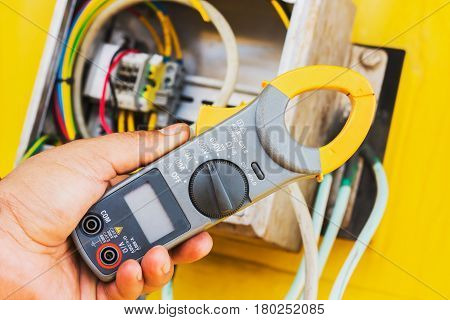 Clamp amp meter Hand of electrician with Clamp amp meter for check or measureing the current of electrical system