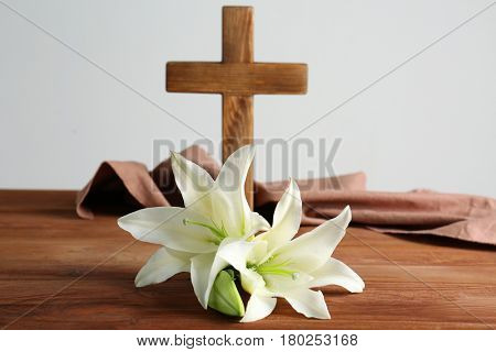 White lily and blurred wooden cross on background