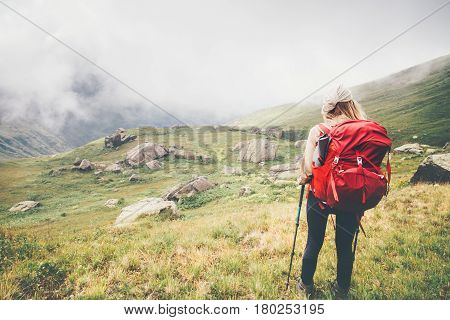 Traveler Woman hiking in foggy mountains Travel Lifestyle concept adventure summer vacations outdoor mountaineering with backpack alone into the wild