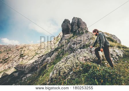 Traveler Man climbing at rocky mountains Travel Lifestyle concept adventure summer vacations outdoor hiking activity
