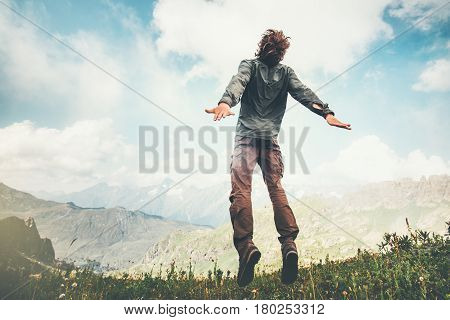 Man jumping up at mountains to clouds sky Lifestyle Travel emotional euphoria success concept adventure summer vacations outdoor