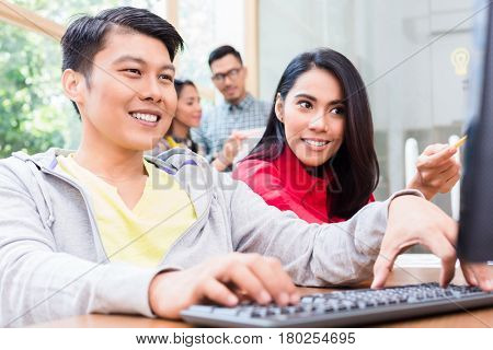 Cheerful young employee working on a desktop PC while following helpful indications from his experienced female colleague in the office