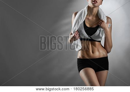 Feeling fit. Female fitness trainer wearing sports clothing posing with a towel around her neck on blue background looking away copyspace on the side