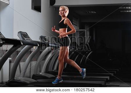 Cheerful young beautiful fitness woman smiling to the camera while running on a treadmill at the gym workout exercising lifestyle health motivation positivity hobby sportsperson sexy hot body slim.
