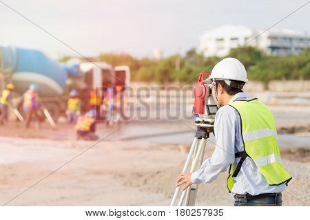 Asian Land surveyor and Asian civil engineer working with his equipment.