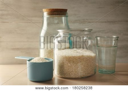 Kitchen ware with rice and water on wooden table