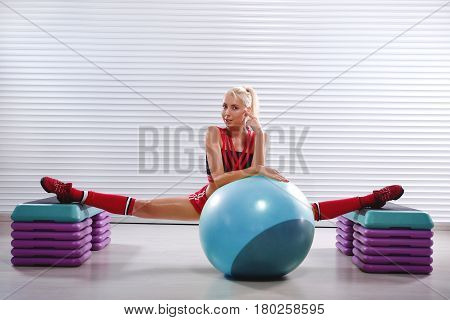 Professional female gymnast smiling to the camera leaning on a fit ball while doing splits working out at her fitness studio sports energy positivity vitality people toning personal trainer gym.