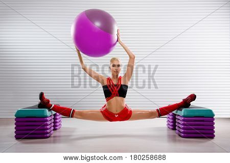 Stunning flexible female gymnast holding a fit ball over her head while practicing splits at the fitness studio flexibility stretching exercise workout trainer body strength motivation sports concept.