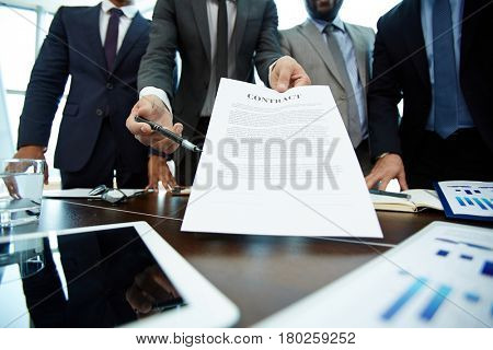 Close-up shot of male hands holding contract and pen and passing them to business partner, table surface with documents and stationery on foreground