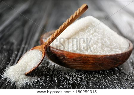 Decorative brown spoon and plate with white granulated sugar on black wooden background