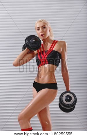 Vertical shot of a beautiful fit and toned athletic woman working out with weights sweating at the gym muscles toning shaping exercising biceps abs sexy hot strong confidence motivation concept.