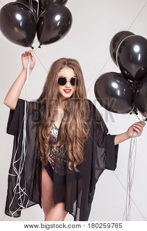 Pretty girl with good body and long hair posing with baloons in her hands.
