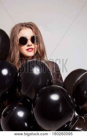 Beautiful young girl wearing glasses and hiding behind baloons.