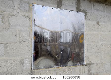 A Window Made Of Plexiglas In A Concrete Wall. A Window With A Reflective Sticker.