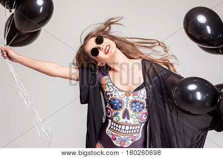 Happy beautiful girl waving her head. Girl holding baloons and wearing glasses.