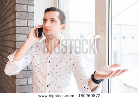 Serious young man in white shirt speaking over phone with interrogative expression
