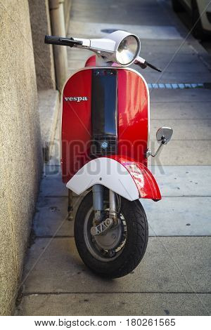 Classic scooter Vespa parked on a public street in France. Perpignan 14.07.2014. Vintage scooter wheel and body design details.Treviglio Lombardy Italy.