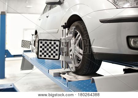 Grid sensor sets mechanic on auto. Car stand with sensors wheels for alignment camber check in workshop of Service station