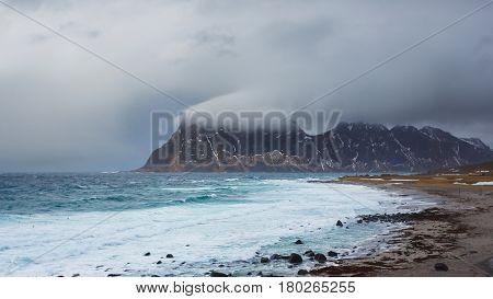 Dark rainy clouds over the Uttakliev beach in Lofoten islands winter time