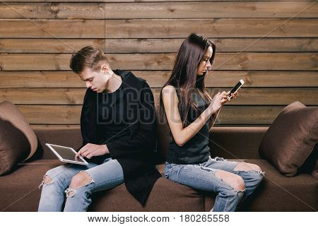 man and woman in a quarrel. They sit on a brown sofa and look at the tablet and phone. Concept of quarrel, divorce, mistrust