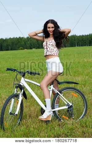 smiling woman on bicycle in the field