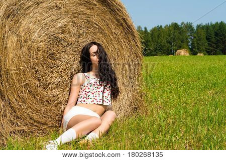 beautiful brunette sleeping on haystack in summer