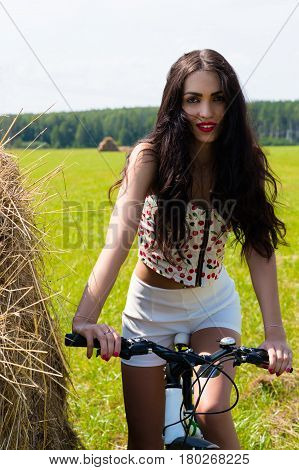 charming brunette cycling in the field outdoors