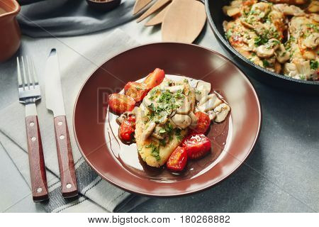 Plate with delicious chicken marsala and tomatoes on table