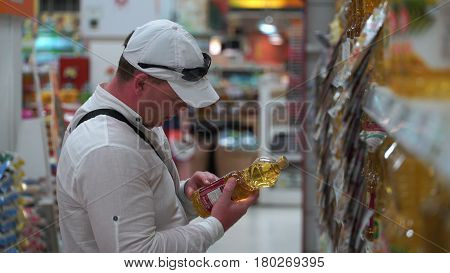 man buys sunflower oil in a supermarket