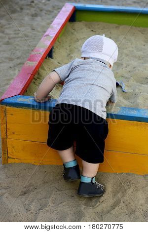 Kid playing on the Playground in the warm time of the year. The child digging in the children's sandbox. Rear view.