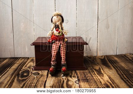 toy redhood sitting on wooden box wood background