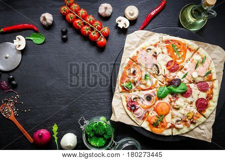 Food frame with italian pizza, ingredients, vegetables and spices on dark background. Flat lay, top view. Food background