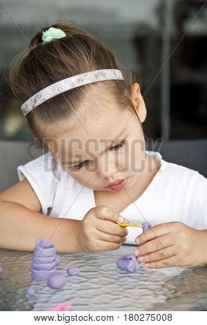 Little cute asian girl sculpts from clay