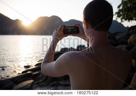 Brunet photographs standing on sea shore, sunset
