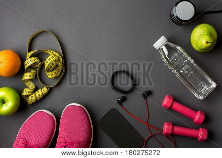 Athlete's set with female clothing and bottle of water on dark gray background. Top view. Still life. Copy space