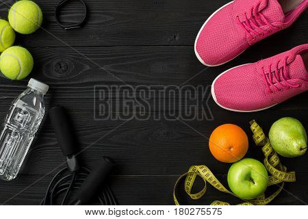 Athlete's set with female clothing and bottle of water on dark background. Top view. Still life. Copy space