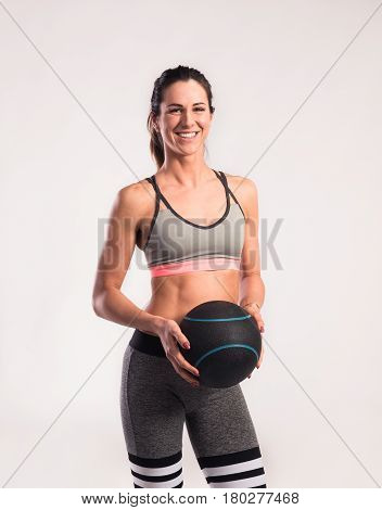 Attractive young fitness woman in sports bra and gray leggings holding medicine ball. Slim waist, perfect fit female body. Studio shot on gray background.