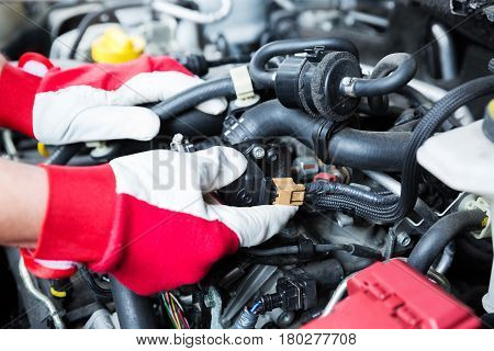 auto mechanic checking car engine electrical connections