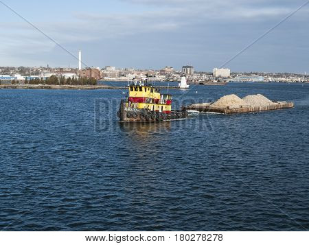 New Bedford Massachusetts USA - March 17 2017: Tug towing barge full of dirt leaving New Bedford harbor