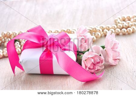 Mother's Day holiday card gift box with bow pink carnations and pearls beads on a wooden table
