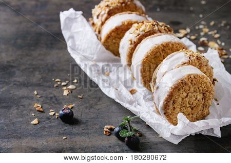 Set of homemade ice cream sandwiches in oat cookies with almond sugar crumbs, blueberries and mint on baking paper over dark metal texture background. Close up
