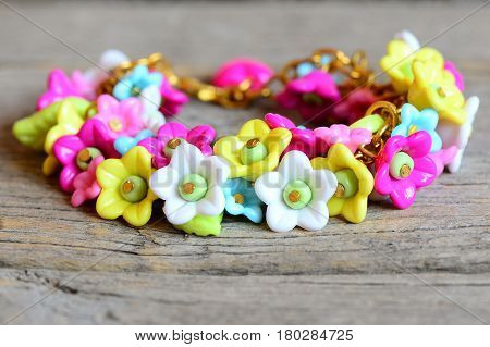 Bright bracelet isolated on old wooden background. Bracelet made of colorful plastic flowers, leaves and beads. Accessory for a little girl. Closeup