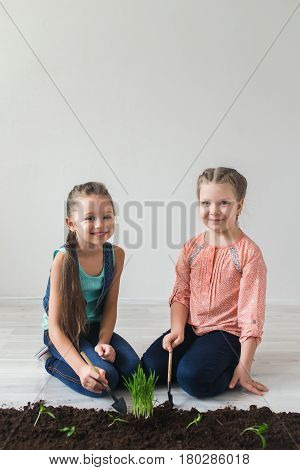 Children and symbol of Earth Day in the white room.