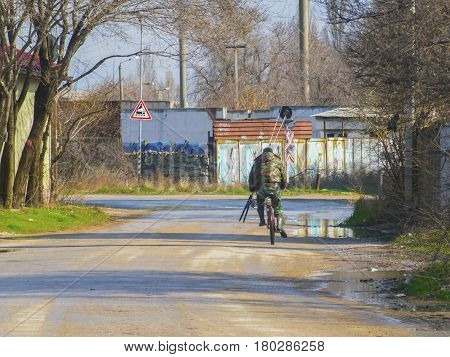 The fisherman with a fishing rod rides on a bicycle