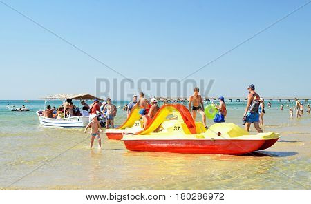 ANAPA, RUSSIA - SEPTEMBER 12, 2016: Beach vacation in Black Sea resort. Children play in shallows near catamarans. Group of tourists going on sea excursion in small boat under thatched roof