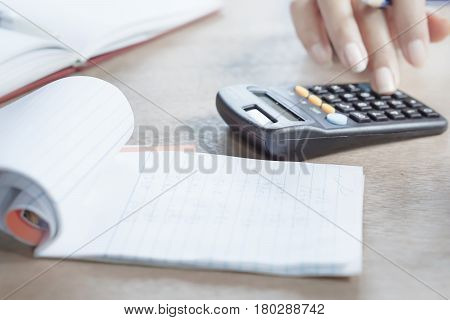 hand typing on a calculator during tax season with a notebook in the foreground