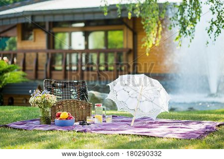 Beautiful picnic setting on sunny day. Outdoor picnic set lying on grass.