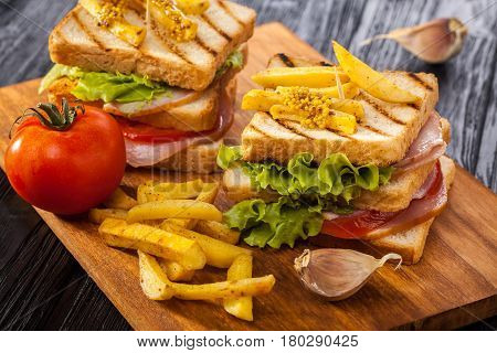 club sandwich with Tomato lettuce bacon ham and french fries on the black wooden table