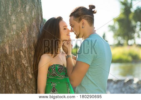 romantic woman and man lean on tree. Guy loves his girlfriend. Walk in park. Nice love story of romantic couple.