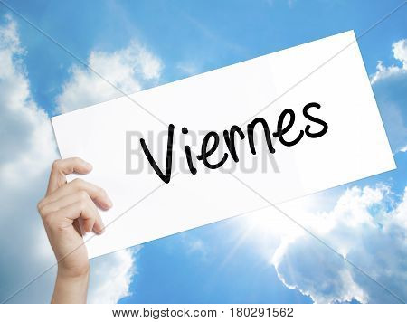Man Hand Holding Paper With Text Viernes (friday In Spanish) . Sign On White Paper. Isolated On Sky